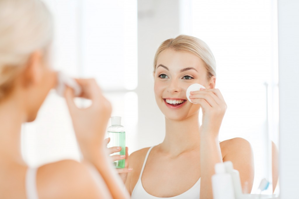 smiling young woman applying lotion to cotton disc for washing her face at bathroom