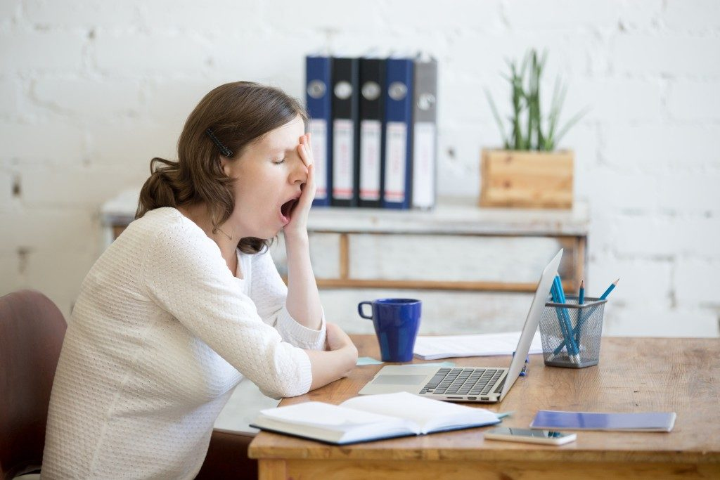 woman yawning in front of her laptop