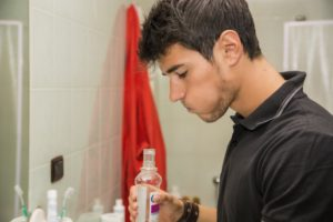 man using mouthwash