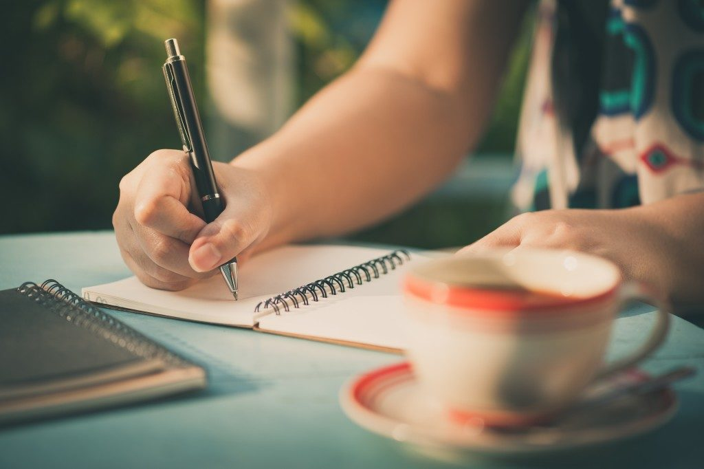 Woman hand writing journal on small notebook at outdoor area in cafe with morning scene and vintage filer effect