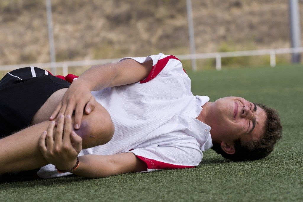 Football player experiencing pain in his knee