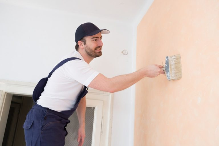 man painting the walls of the house