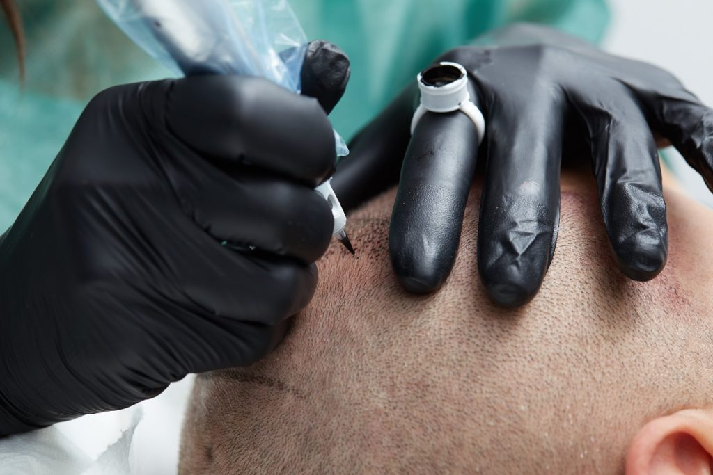 cosmetologist making permanent makeup on man's head