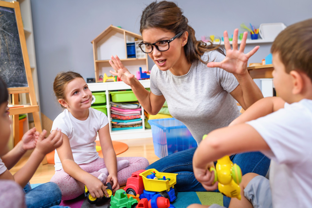 woman playing with young children