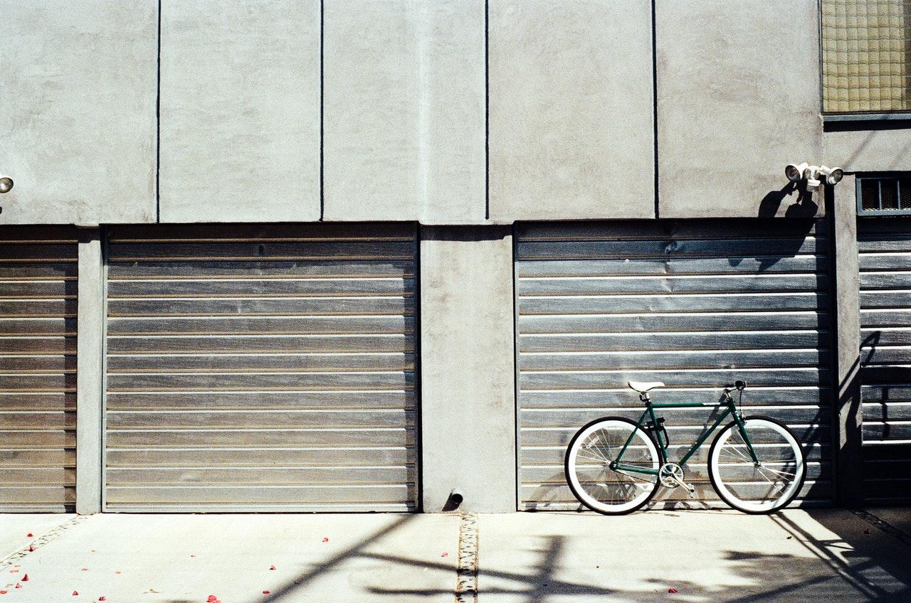 fixed gear bike in front of 2 garage doors