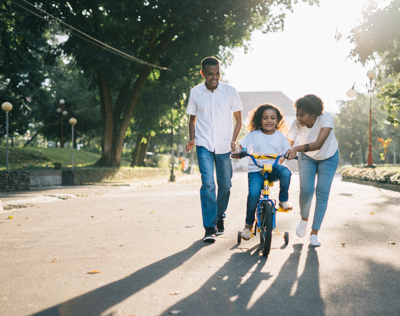 parents teaching child how to ride a bike