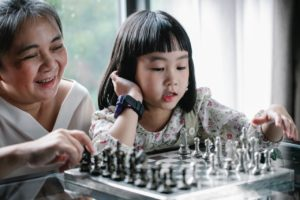 kid playing chess with her mother