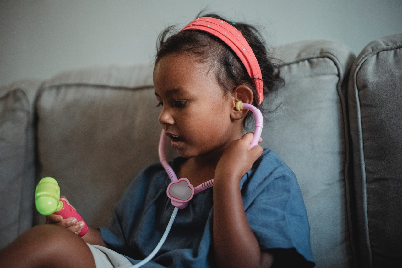 kid playing with a toy stethoscope