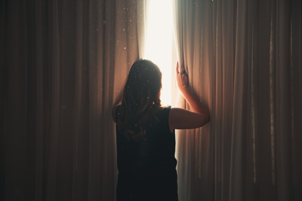 woman opening the curtains