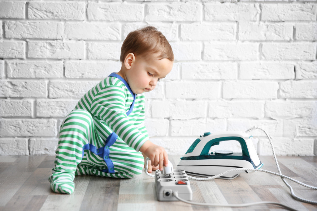 Little child playing with iron and electric power