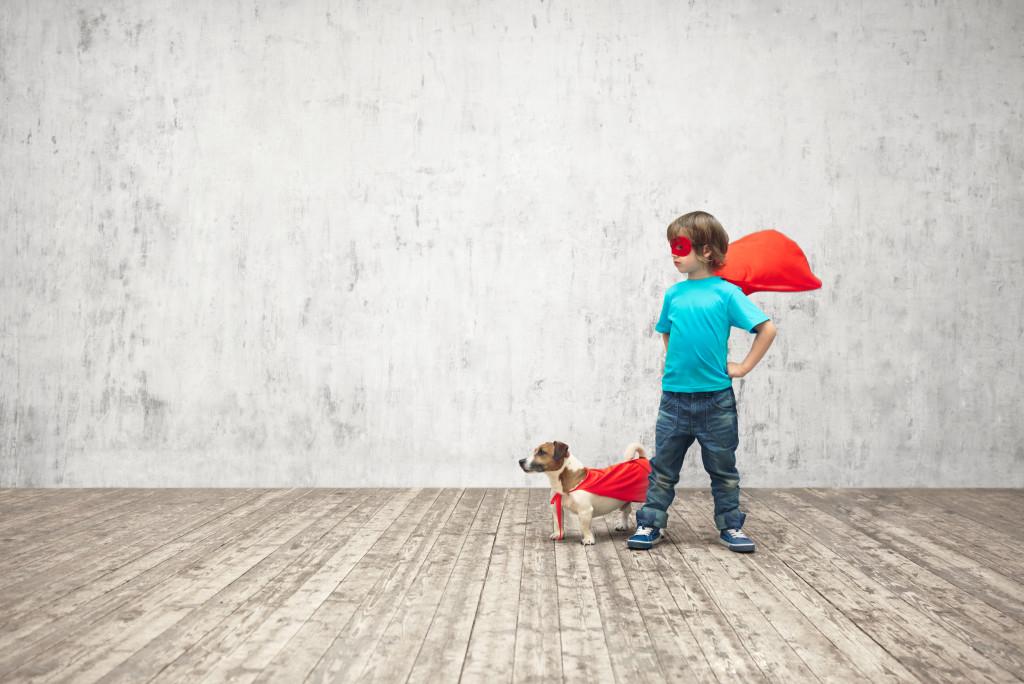 child and dog wearing superhero costumes