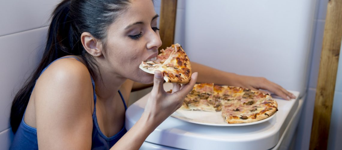 girl eating pizza on top of toilet