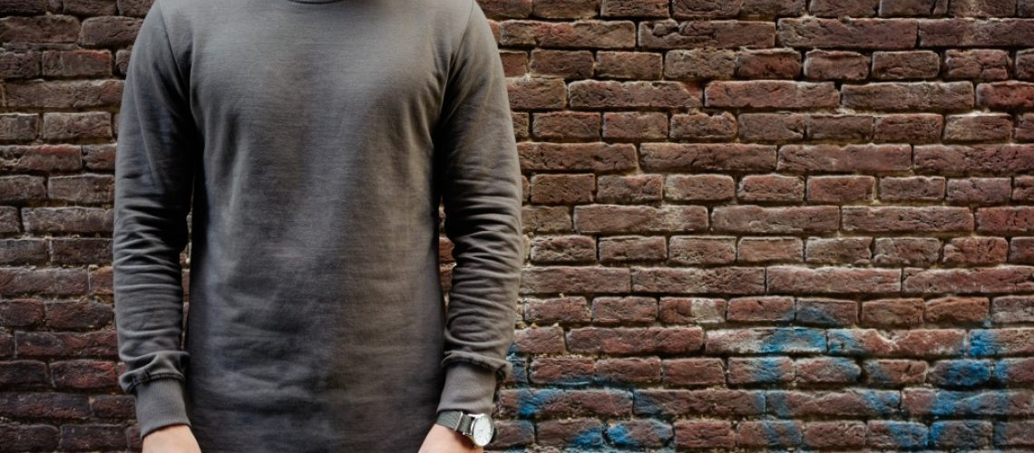 man wearing a black long sleeve shirt with brick walls as the background
