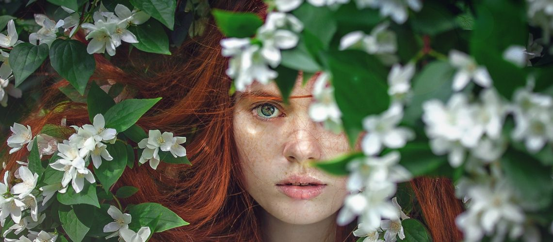 woman behind some leaves